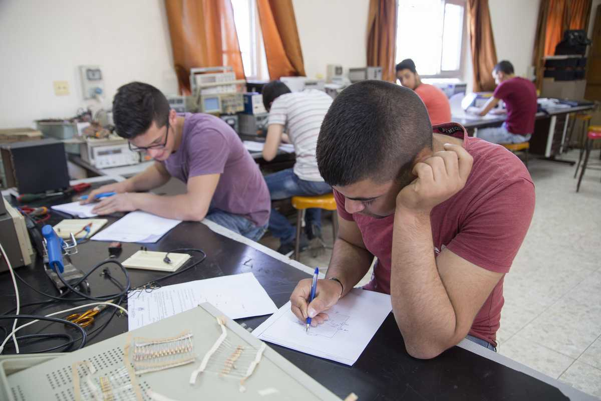 Zwei Jungen sitzen an Tischen und arbeiten in Heften