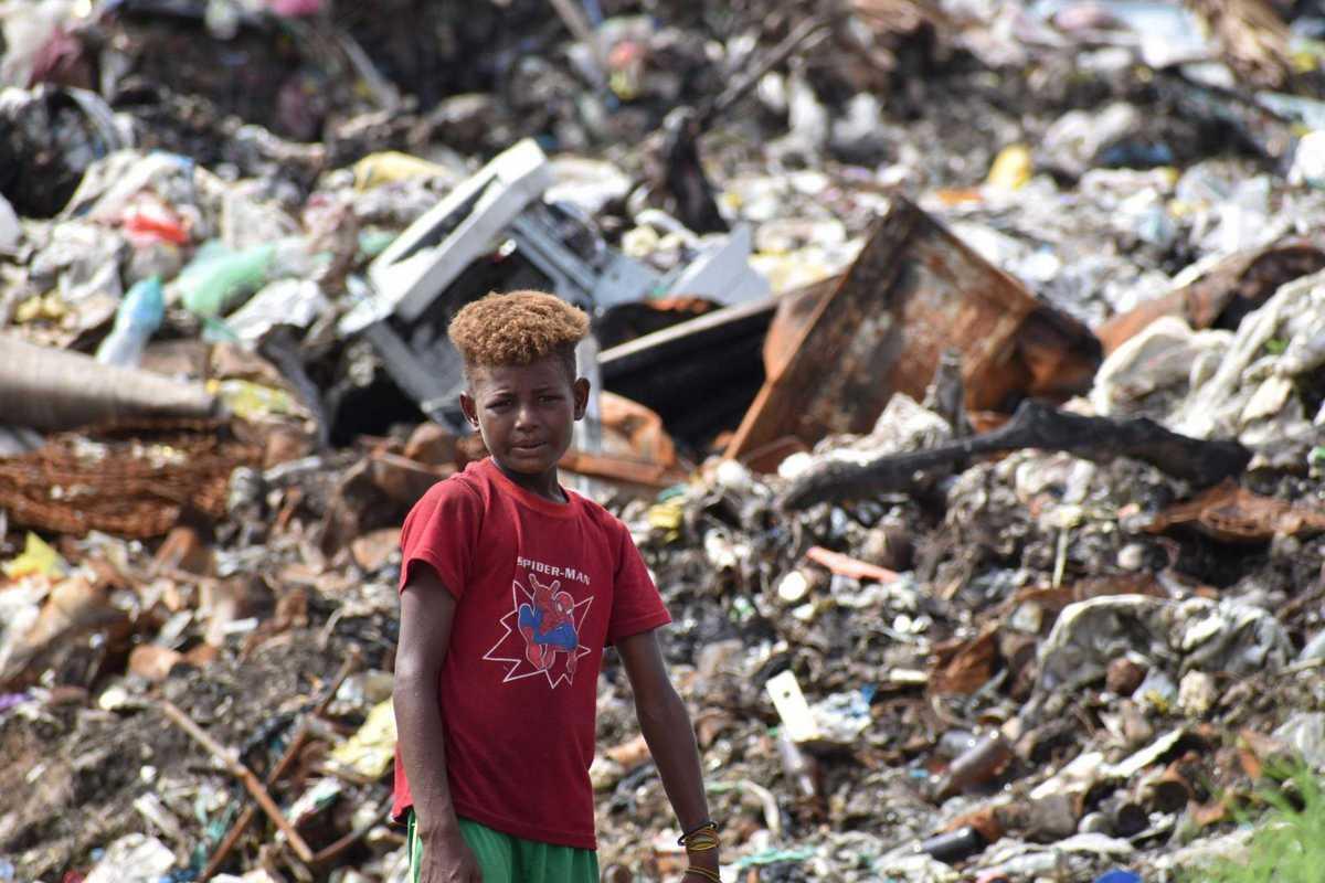 Junge steht vor einem Müllberg