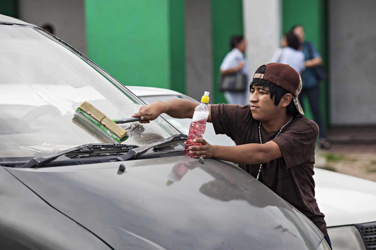 Armando putzt die Scheiben eines Autos