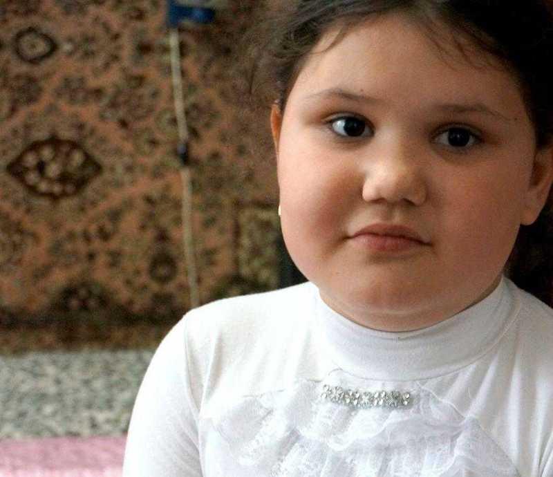 Ana sitzt auf ihrem Bett und hält ein Passfoto ihrer Mutter in der Hand