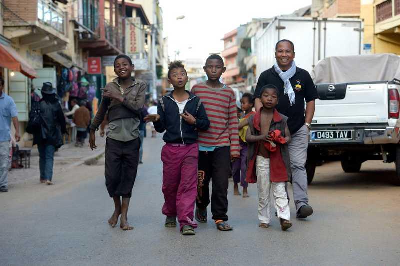 Pater Jannot und lachende Kinder ziehen durch die Straße
