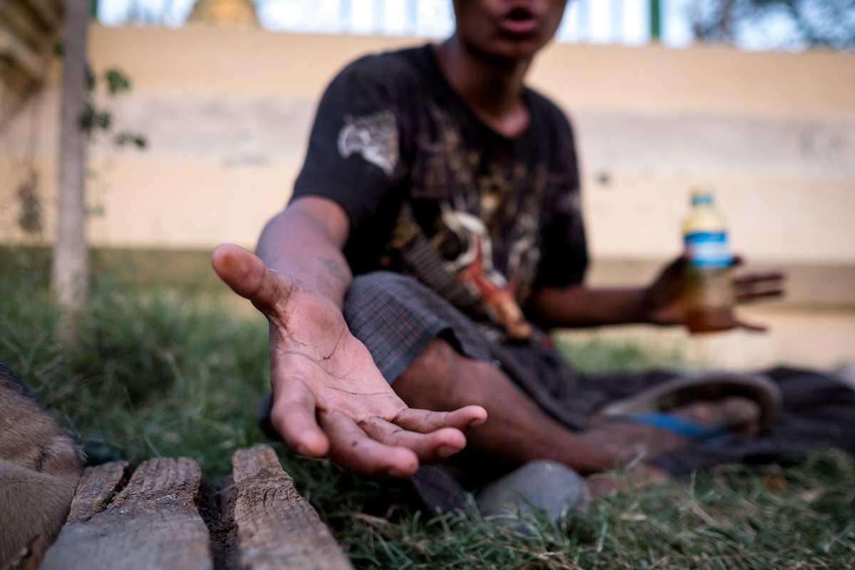 Straßenjunge sitzt auf dem Boden und streckt die Hand aus