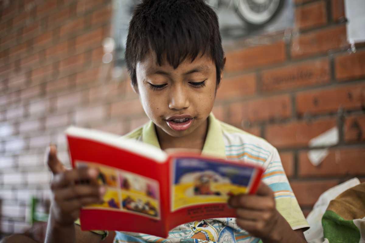 Àlvaro sitzt auf seinem Bett und liest ein Buch.